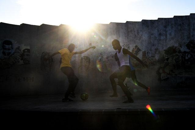 People play football in the Haitian capital Port-au-Prince, on April 10, 2019. (Photo by Chandan Khanna/AFP Photo)