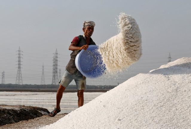 A labourer empties a salt basket in a salt pan in Mumbai, April 10, 2017. (Photo by Shailesh Andrade/Reuters)