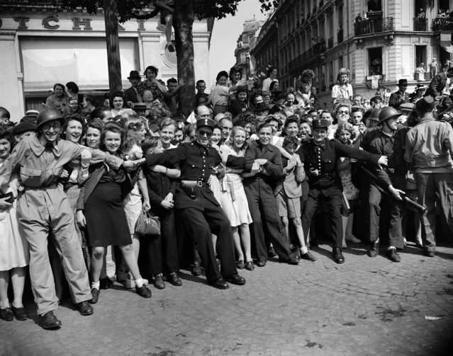 In this August 26, 1944 file photo, gendarmes and F.F.I. hold back crowds of people as they throng the streets to see General Charles De Gaulle in Paris. The fighting for the liberation of Paris took place from August 19 to August 25, 1944. (Photo by Laurence Harris/AP Photo/File)