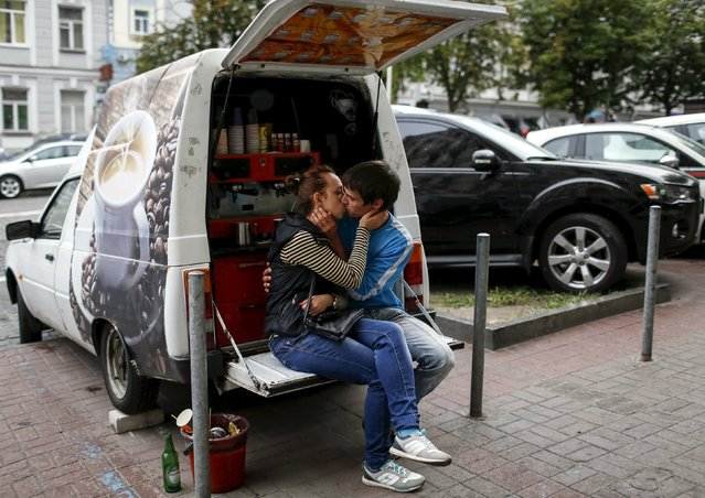 A street vendor of coffee kisses his girlfriend as he waits for clients in central Kiev, Ukraine, July 13, 2015. (Photo by Gleb Garanich/Reuters)