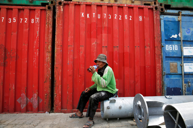 A worker drinks tea as he rests beside containers at Sunda Kelapa harbour in Jakarta, Indonesia May 3, 2016. (Photo by Reuters/Beawiharta)