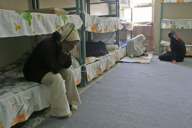 Iranian women try to hide their faces inside a prison cell in the women's section of the Evin prison in north Tehran on Tuesday, 13 June 2006. Most of the convicts are jailed for drugs use. (Photo by Abedin Taherkenareh/EPA)