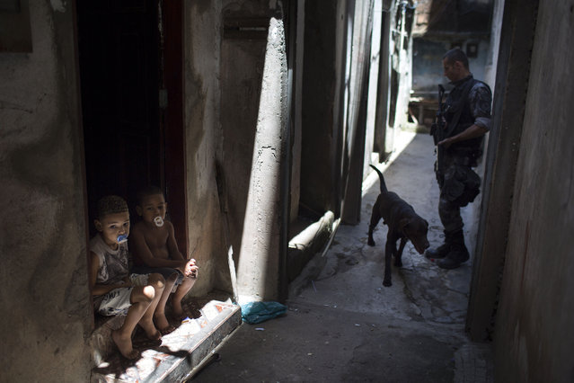 "Boys sit on the stoop of their home as a police officer patrols nearby with a sniffer dog during an operation in the Jacarezinho slum in Rio de Janeiro, Brazil, Tuesday October 16, 2012. The Jacarezinho slum will now become part of a state program that establishes so-called ""peacekeeping police units"", in shantytowns previously held by drug traffickers. (Photo by Felipe Dana/AP Photo)"
