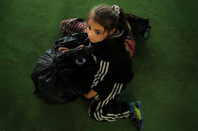 A Syrian girl who is newly displaced by the Turkish military operation in northeastern Syria, sits next to her belongings upon her arrival at the Bardarash camp, north of Mosul, Iraq, Wednesday, October 16, 2019. The camp used to host Iraqis displaced from Mosul during the fight against the Islamic State group and was closed two years ago. The U.N. says more around 160,000 Syrians have been displaced since the Turkish operation started last week, most of them internally in Syria. (Photo by Hussein Malla/AP Photo)