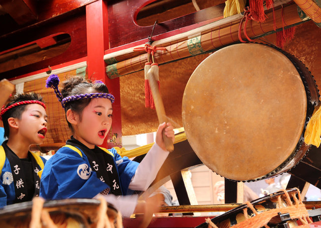 Japanese children dressed traditional festival costumes as perform Taiko drum on the huge paper doll cart of historical figure during the Mikuini annual festival on May 20, 2014 in Sakai, Japan. The annual festival takes place from May 19-21 and is attended by thousands of visitors. During the festival people dressed in traditional Japanese costumes pull carts carrying 6 meter high dolls of Japanese historical figures through the narrow streets. The origins of the festival are unclear but its history can be traced back more than 250 years. (Photo by Buddhika Weerasinghe/Getty Images)
