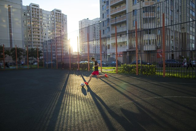 """In this July 2, 2015 photo, a teenager plays soccer in the last rays of the setting sun at a playground in Moscow, Russia. While the Brazilians learn to play on the streets or the beach, Russian children have the """"dvor"""", the yard space between towering apartments blocks. Yard football is a national tradition, and the asphalt pitches are often the first step in the careers of future stars of the Russian national team. (Photo by Alexander Zemlianichenko/AP Photo)"""