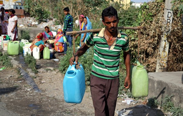 An Indian man carries containers filled with drinking water after taking it from a public tap at a roadside on the outskirts of Jammu, the winter capital of Kashmir, India, 23 May 2016. Hundreds of households in mostly poor neighborhoods in Jammu depend on leaking water pipes during summer as they have no direct supply of water at home. (Photo by Jaipal Singh/EPA)