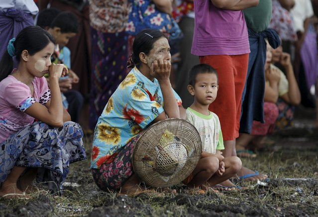 People waits for aid at a stadium used as a temporary refugee camp in Kawlin township, Sagaing division, Myanmar, July 21, 2015. (Photo by Soe Zeya Tun/Reuters)