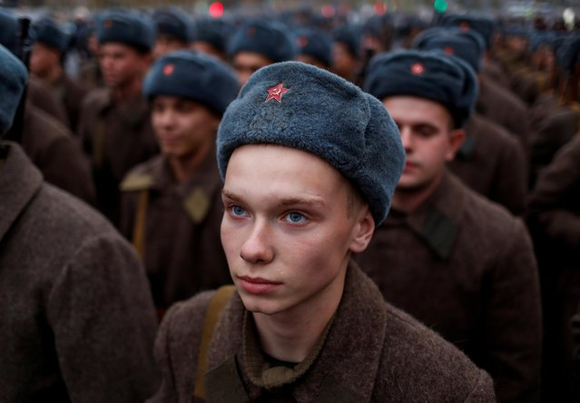 A Russian Army member, dressed in historical uniform, looks on before a rehearsal for a military parade to mark the anniversary of a historical parade in 1941, when Soviet soldiers marched towards the front lines, at the Red Square in Moscow, Russia November 5, 2019. (Photo by Maxim Shemetov/Reuters)