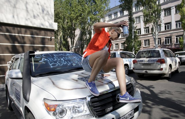 "A demonstrator jumps from a vehicle of the Organisation for Security and Co-operation in Europe (OSCE) during a protest to demand what protesters say is true information from the OSCE about the shelling in Donetsk, Ukraine, July 23, 2015. The graffiti reads, ""Stop moronic war!"". (Photo by Alexander Ermochenko/Reuters)"