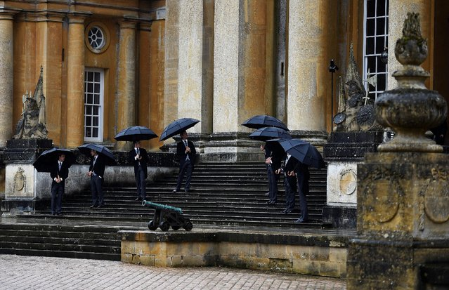 Doormen stand in the rain as they wait for guests to arrive for the Dior Cruise 2017 Collection fashion show at Blenheim Palace in Woodstock, Britain May 31, 2016. (Photo by Dylan Martinez/Reuters)