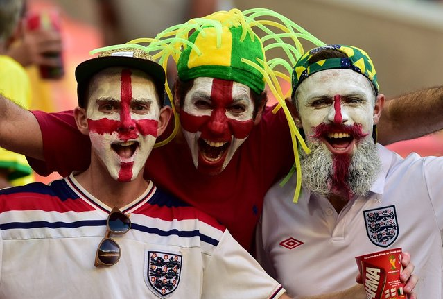 England fans with their faces painted in the colours of their national flag cheer before the kick-off of a Group D football match between England and Italy at the Amazonia Arena in Manaus during the 2014 FIFA World Cup on June 14, 2014. (Photo by Giuseppe Cacace/AFP Photo)
