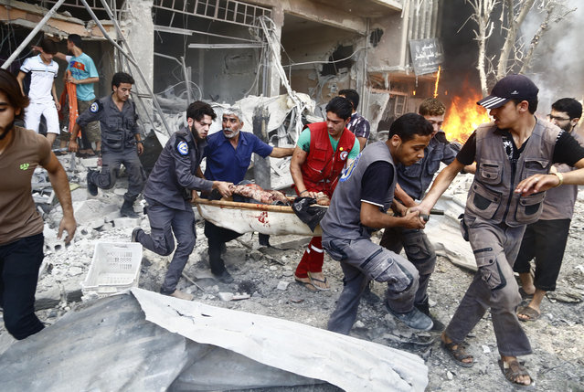 Emergency services and civilians carry a serverely wounded man on a stretcher following an air strike on Douma, a rebel-held suburb east of the Syrian capital Damascus, on July 27, 2015. (Photo by Sameer Al-Doumy/AFP Photo)