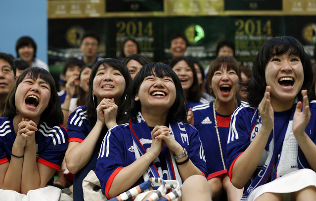 Fans of Japan's national soccer team celebrate after Japan's Keisuke Honda scored against Ivory Coast as they watch their team play in the 2014 World Cup at a public viewing event in Tokyo June 15, 2014. (Photo by Issei Kato/Reuters)