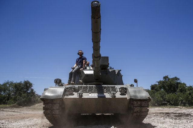 In this May 24, 2017, photo, DriveTanks.com cadre Glenn Fleming, bottom center, shows Casey Jones, left, how to drive a German Leopard 1A4 tank during an Allies and Axis all-day experience at Ox Ranch in Uvalde, Texas. (Photo by Michael Ciaglo/Houston Chronicle via AP Photo)