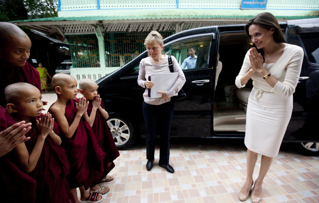 Angelina Jolie, right, pays respect to Buddhist novice monks upon arrival at a monastery to meet with religious leaders from Myanmar Interfaith Group Friday, July 31, 2015, in Yangon, Myanmar. The Hollywood actress arrived in Myanmar, for her first visit to the country Thursday to learn more about the situation in the country and encourage efforts to build a peaceful and inclusive future for all its people. (Photo by Khin Maung Win/AP Photo)