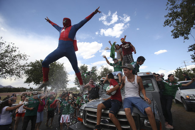 A Mexican soccer fan, dressed in a Spiderman costume, jumps from a vehicle as he celebrates Mexico's 2014 World Cup soccer match win over Croatia, in Ciudad Juarez June 23, 2014. (Photo by Jose Luis Gonzalez/Reuters)