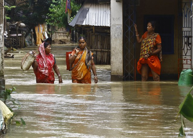 Flood-affected people carry their belongings as they move to safer grounds along a flooded street at West Midnapore district in West Bengal, India, August 4, 2015. (Photo by Rupak De Chowdhuri/Reuters)