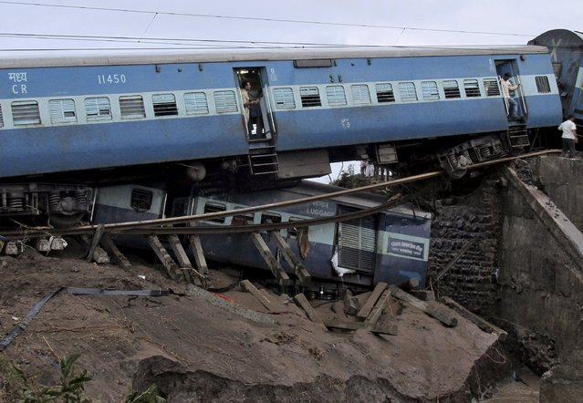 Damaged coaches of passenger trains are pictured after they derailed near Harda in Madhya Pradesh, India, August 5, 2015. Two express trains derailed into a river in central India overnight after flood water weakened the tracks, killing 21 people, state officials said on Wednesday, reigniting criticism about lack of safety on the world's fourth-largest rail network. (Photo by Reuters/Stringer)