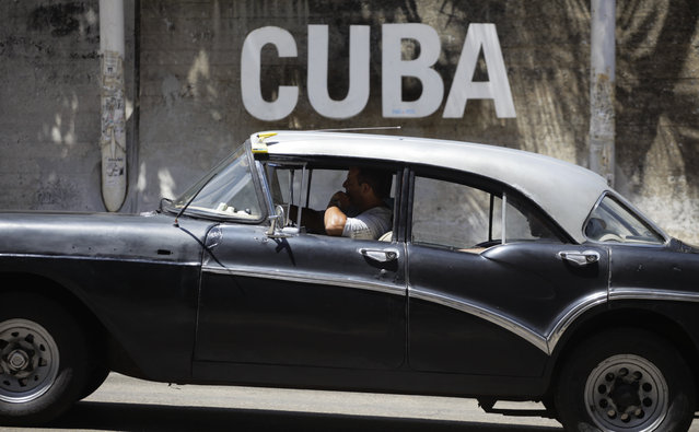 """A man drives his taxi past a Cultural Center with the word """"Cuba"""" on it, in Havana, Cuba, Tuesday, April 14, 2015. (Photo by Desmond Boylan/AP Photo)"""