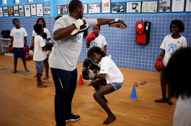 Teacher Alan (L) trains children during an exercise session at a boxing school, in the Mare favela of Rio de Janeiro, Brazil. (Photo by Nacho Doce/Reuters)