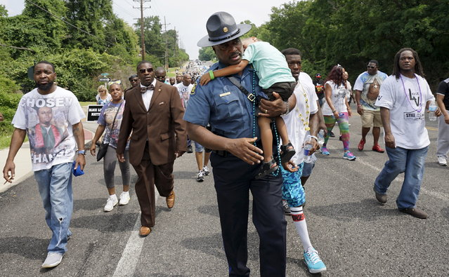 Capt. Ron Johnson of the Missouri State Highway Patrol carries sleeping Quinn Edwards, 4, after taking him from his father Frankie (in shorts next to Johnson) to put him on his UTV during a protest march in Ferguson, Missouri August 8, 2015. (Photo by Rick Wilking/Reuters)
