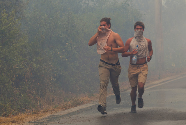 Tourists run through smoke during a forest fire at Lustica peninsula near Tivat, Montenegro, July 17, 2017. (Photo by Stevo Vasiljevic/Reuters)