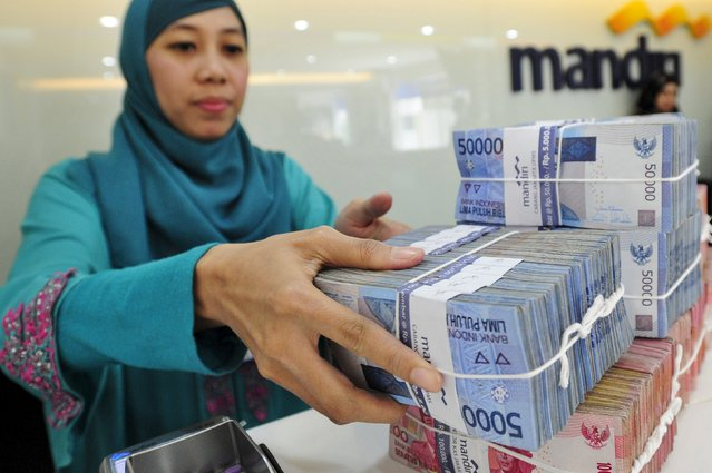 A teller at a Bank Mandiri branch handles Indonesian Rupiah currency during a transaction in Jakarta July 20, 2015 in this photo taken by Antara Foto. The Indonesian rupiah hit a fresh 17-year low on July 23, 2015, as solid U.S. housing data added to expectations the Federal Reserve with hike interest rates as soon as September. (Photo by Wahyu Putro/Reuters/Antara Foto)