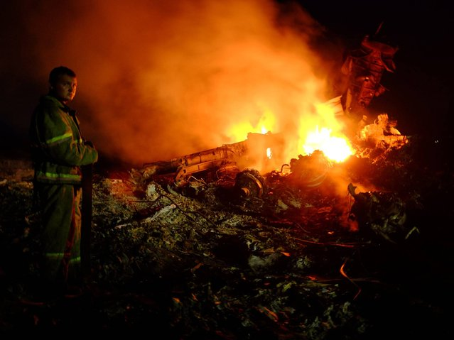A firefighter stands as flames burst amongst the wreckages of the Malaysian airliner near the town of Shaktarsk, in rebel-held east Ukraine. (Photo by Alexander Khudoteply/AFP Photo)