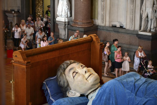 Visitors look at a giant puppet of a grandmother sleeping on a bed inside St George's Hall in Liverpool, northern England July 23, 2014. (Photo by Nigel Roddis/Reuters)