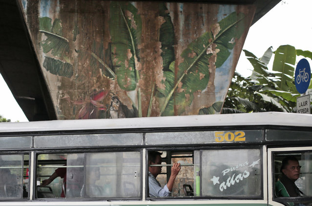 In this Wednesday, Oct. 12, 2016 photo, passengers sit inside a city bus as it drives past a mural depicting coconut trees in Jakarta, Indonesia. One of the strange sights in Indonesia, an ecologically rich archipelago of more than 13,000 islands, is its capital's fondness for fake greenery at a time when the country is known for cutting down its precious tropical forests at a record rate. (Photo by Dita Alangkara/AP Photo)