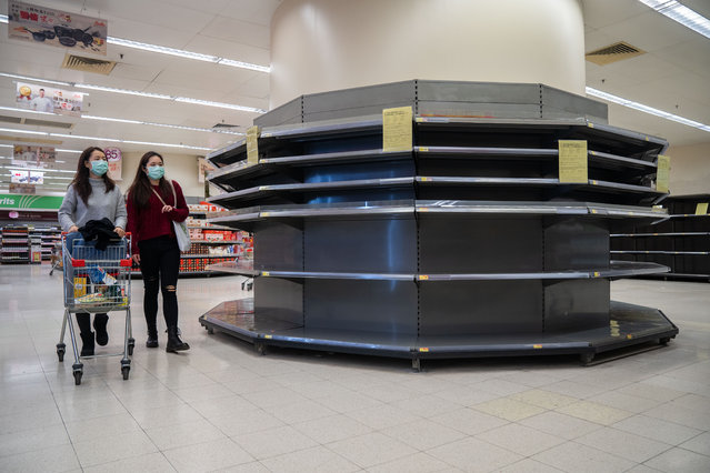 Two shoppers in surgical masks walk past empty supermarket shelves, usually stocked with toilet paper and kitchen rolls in Hong Kong, China on February 12, 2020. Panic is growing in the city as the authorities confirm the 50th case of the Covid-19 coronavirus. (Photo by Geovien So/SOPA Images/Rex Features/Shutterstock)