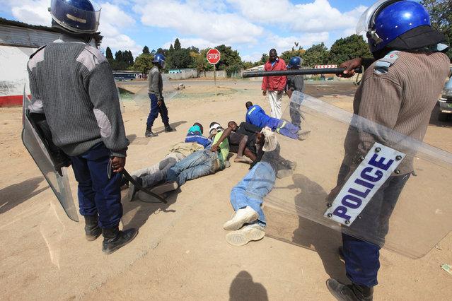 Armed Zimbabwean police surround rioters in Harare, Monday, July, 4, 2016. (Photo by Tsvangirayi Mukwazhi/AP Photo)