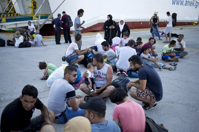 """Syrian refugees sit on the ground following their arrival onboard """"Eleftherios Venizelos"""" passenger ship at the port of Piraeus near Athens, Greece, August 20, 2015. (Photo by Stoyan Nenov/Reuters)"""