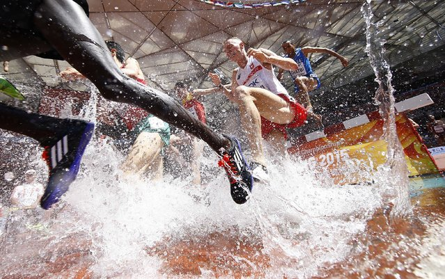 Competitors take part in the men's 3000 metres steeplechase heats at the 15th IAAF World Championships at the National Stadium in Beijing, China August 22, 2015. (Photo by Kai Pfaffenbach/Reuters)