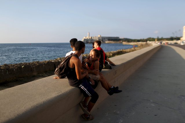 Pantomime artist Sheila Marrupe, 15, (C), relaxes with friends at the seafront Malecon in Havana, May 21, 2015. (Photo by Alexandre Meneghini/Reuters)