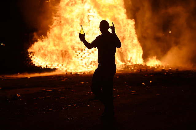 A man dances in front of a bonfire burning in the Shankill Road area ahead of the Twelfth of July celebrations held by members of the Orange Order in Belfast, Northern Ireland, July 12, 2016. (Photo by Clodagh Kilcoyne/Reuters)