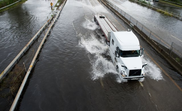 A trailer truck traverses a flooded street at Sunrise Highway following heavy rains and flash flooding August 13, 2014 in Bayshore, New York. The south shore of Long Island along with the tri-state region saw record setting rain that caused roads to flood entrapping some motorists. (Photo by Andrew Theodorakis/Getty Images)