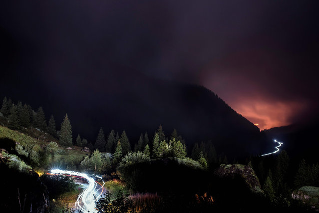 In this long exposure photo, lights of ultra- trailers competing illuminate the way on the Balme path, on September 1, 2017 in Les Contamines Montjoie, during the 15 th edition of the Mount Blanc Ultra Trail (UTMB), a 170 km race around the Mont Blanc crossing France, Italy and Switzerland. (Photo by Jeff Pachoud/AFP Photo)