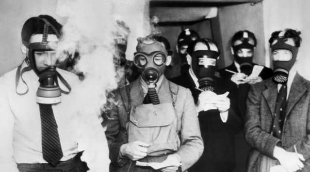 Left to right: John Fremlin, research physicist, wears a German gas mask; Mr. Sander, air raid precautions instructor, wears an army mask; and Lord Forces and M. Dunne wear civilian type masks, which sell in England for about 60 cents. They?re in a chamber in London testing the masks, jotting down notes as the fumes of the gas swirl about them, on August 27, 1938. (Photo by AP Photo)