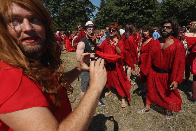 """Participants dressed as singer Kate Bush from her 1978 video to her song """"Wuthering Heights"""" snap phots of each other after attempting to create a new world's record for the most people dancing in costume to the song at once at Tempelhofer Feld park on July 16, 2016 in Berlin, Germany. (Photo by Sean Gallup/Getty Images)"""
