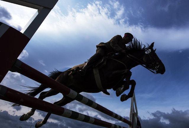 """German Josef Fuchs and his horse """"Aragon"""" clear a hurdle during the fault and style jumping at the 4th International Open German Cavalry Championship in Crawinkel, central Germany, Friday, September 8, 2017. Teams and single riders from different nations compete in historic riding competitions, such as tests with lance and saber, dressage and steeplechases. (Photo by Jens Meyer/AP Photo)"""