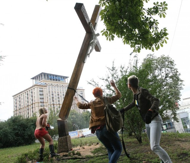 Ukraine FEMEN-activist Cuts Down Cross in Russian Female Punk Rock Band Protest