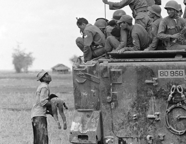 A father holds the body of his child as South Vietnamese Army Rangers look down from their armored vehicle March 19, 1964. The child was killed as government forces pursued guerrillas into a village near the Cambodian border. This photo won Faas the Pulitzer Prize for Photography in 1965. (Photo by Horst Faas/AP Photo)