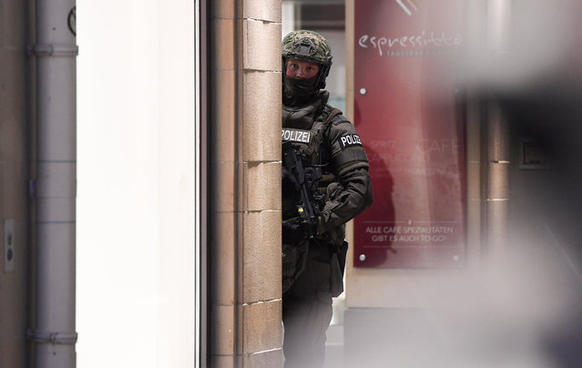 Police officer stands in downtown Munich after a shooting was reported there in Munich, southern Germany, Friday, July 22, 2016. Several people have been reported to be killed. (Photo by Sven Hoppe/DPA via AP Photo)