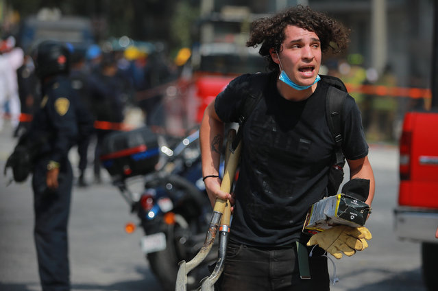 A man carries shovels and gloves as he looks for victims amid the ruins of a building knocked down by a magnitude 7.1 earthquake that jolted central Mexico damaging buildings, knocking out power and causing alarm throughout the capital on September 19, 2017 in Mexico City, Mexico. The earthquake comes 32 years after a magnitude-8.0 earthquake hit on September 19, 1985. (Photo by Hector Vivas/Getty Images)