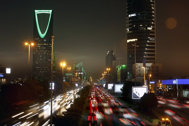 In this September 22, 2019 file photo taken with a slow shutter speed, vehicles pass in front of the landmark Kingdom Tower, at left, during celebrations marking Saudi 89th National Day, in Riyadh, Saudi Arabia. (Photo by Amr Nabil/AP Photo/File)