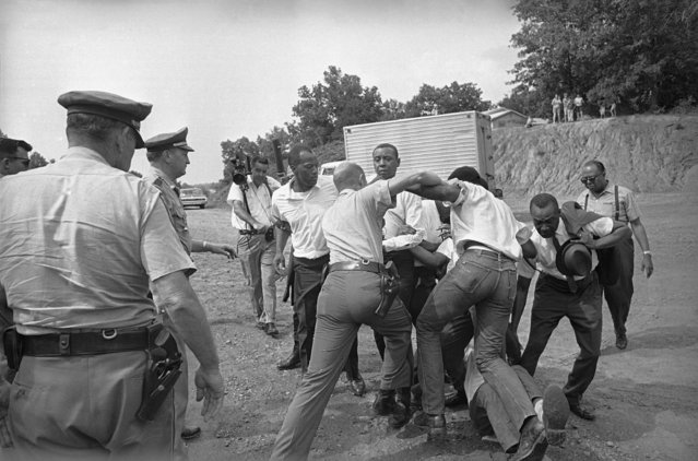 In this June 7, 1966 file photo, Mississippi Highway Patrolmen grapple with black marchers accompanying the Rev. Martin Luther King on a march along U.S. 51 south of Hernando, Miss. Thousands joined a march across Mississippi, started by James Meredith, to challenge a system that condoned violence against black people and suppressed their rights – issues still reverberating in national debates about police violence 50 years later. (Photo by AP Photo)