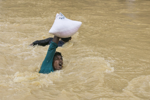 A man struggles to carry supplies across a stream as the monsoon rains continue to make life miserable for the displaced Rohingya September 17, 2017 in Kutupalong, Cox's Bazar, Bangladesh. Nearly 400,000 Rohingya refugees have fled into Bangladesh since late August during the outbreak of violence in the Rakhine state. Recent satellite images released by Amnesty International provided evidence that security forces were trying to push the minority Muslim group out of the country. Myanmar's de facto leader Aung San Suu Kyi cancelled her trip to the United Nations General Assembly in New York, which begins next week, while criticism of her handling of the Rohingya crisis grows and her government has been accused of ethnic cleansing. According to reports, the Rohingya crisis has left at least 1,000 people dead, including children and infants. Dozens of Rohingya Muslims drowned when their Ill-equipped, overloaded boat capsized in rough waters. (Photo by Paula Bronstein/Getty Images)