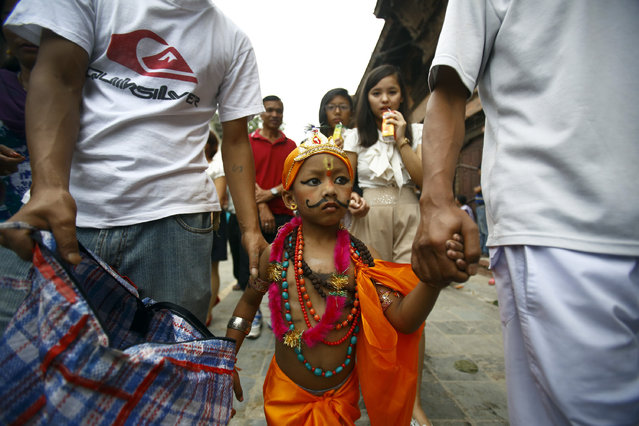 A boy dressed as Lord Krishna participates in a parade to mark the Gaijatra Festival, also known as the festival of cows, in Kathmandu August 22, 2013. (Photo by Navesh Chitrakar/Reuters)